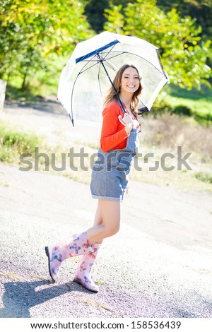 Beautiful young woman holding umbrella out in the rain