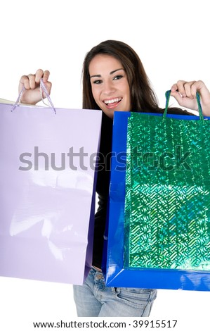 Beautiful young woman holding up shopping bags, happy and smiling, isolated on white background