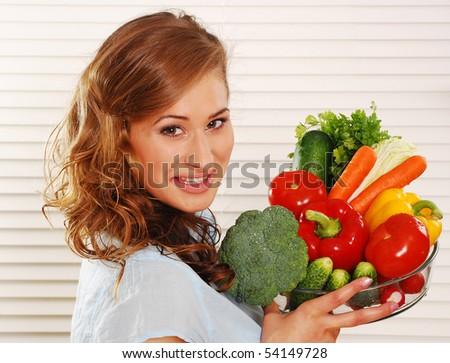 Beautiful young woman holding vegetables