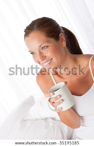 Beautiful young woman holding  white cup of coffee home