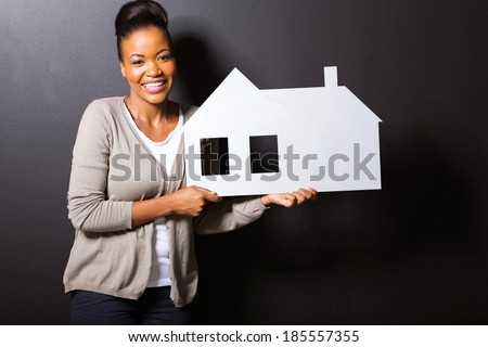 beautiful young woman holding white paper house - stock photo