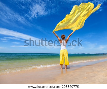 Beautiful young woman holding yellow fabric on wind at the sea beach - stock photo