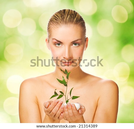 Beautiful young woman holding young plant - stock photo