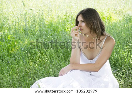 Beautiful young woman holds a daisy chain, sitting in a meadow