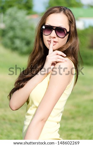Beautiful young woman holds a finger to his lips in token of silence outdoors portrait on the summer day green background - stock photo