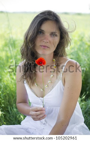 Beautiful young woman holds a poppy, sitting in a romantic meadow - stock photo