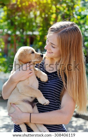 beautiful young woman holds a puppy Labrador. - stock photo