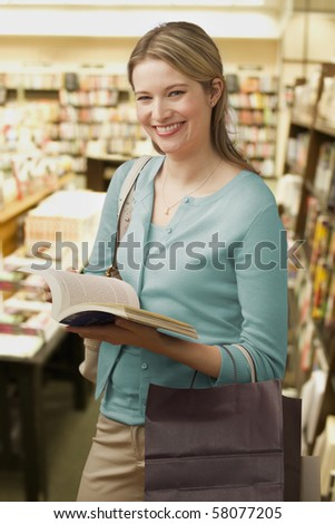 Beautiful young woman holds an open book in a bookstore while smiling towards the camera. Vertical shot. - stock photo