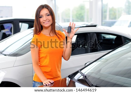 Beautiful young woman holds the key at the car in the Autoshop - stock photo