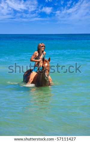 Beautiful young woman horse riding in tropical ocean - stock photo