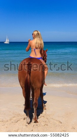 Beautiful young woman horse riding on a tropical beach - stock photo