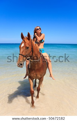 Beautiful young woman horse riding on tropical beach
