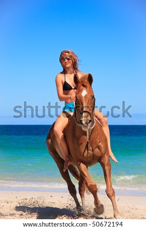 Beautiful young woman horse riding on tropical beach - stock photo