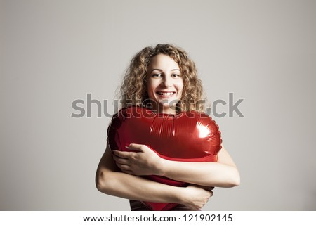 beautiful young woman hugging a heart shaped red balloon and smiling - stock photo