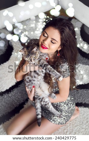 Beautiful young woman hugging and holding cat over boker Christmas Lights background.  - stock photo