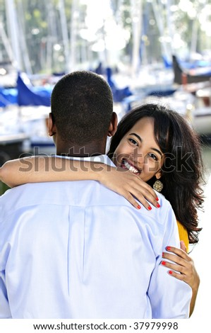 Beautiful young woman hugging boyfriend standing at harbor - stock photo
