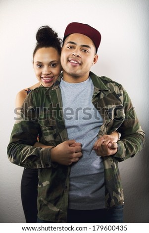 Beautiful young woman hugging her boyfriend from behind. Loving young couple together on grey background. - stock photo