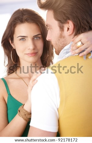Beautiful young woman hugging man, looking at camera.? - stock photo