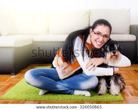 Beautiful young woman hugging miniature schnauzer on the carpet of living room - stock photo
