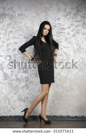 Beautiful young woman in a black dress on abstract gray background. Studio shot - stock photo