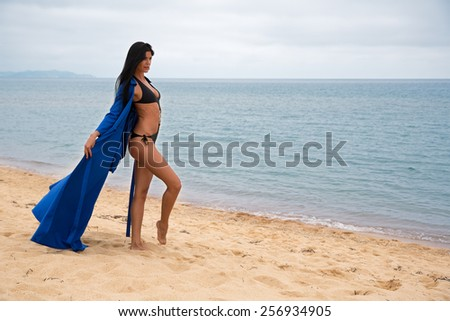 Beautiful young woman in a blue dress and a swimsuit on the beach - stock photo