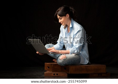 beautiful young woman in a blue shirt with laptop on black background studio - stock photo