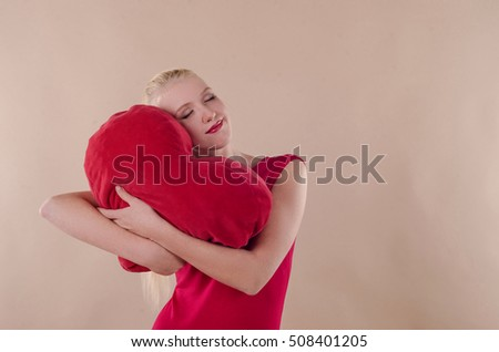 Beautiful young woman in a bright red slinky dress hugging a plush heart on the beige background