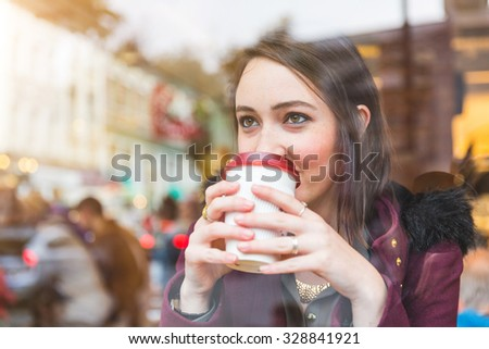 Beautiful young woman in a cafe holding a cup of tea, seen through the window with buildings and lights reflections. She is looking away. Lifestyle concept.