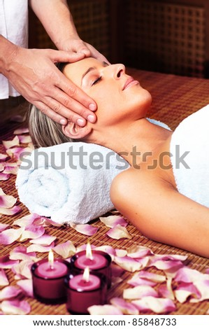 Beautiful young woman in a day spa getting massage. Relax. - stock photo