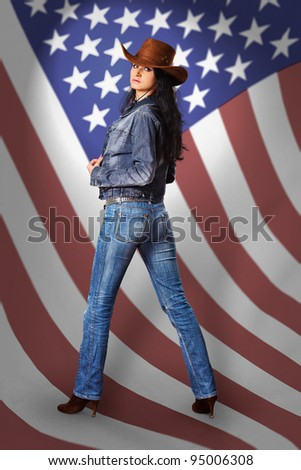Beautiful young woman in a denim dress and a cowboy hat on a background of the American flag