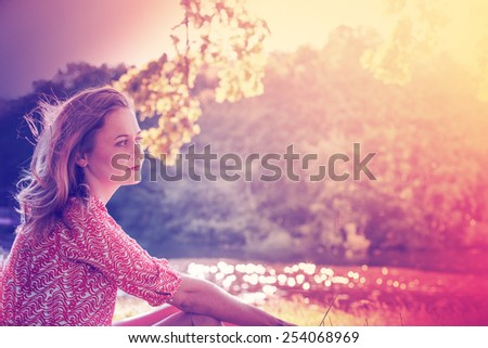 Beautiful young woman in a dress on the nature dreams background - stock photo