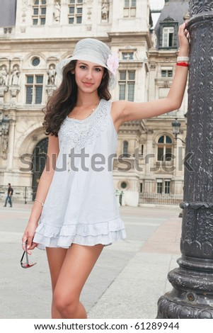 Beautiful young woman in a fashion pose in a typical french plaza in Paris, France. - stock photo