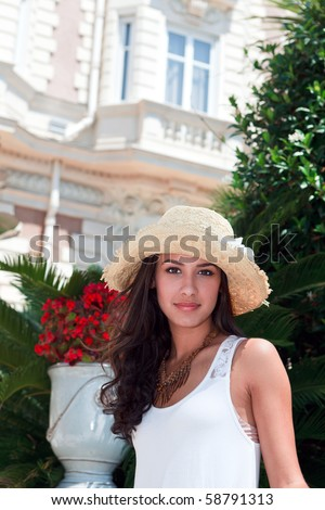 Beautiful young woman in a fashion pose outside a popular hotel in Cannes, France. - stock photo