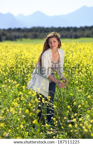 Beautiful young woman in a field of golden yellow rapeseed enjoying the summer sunshine as she picks some of the colorful flowers while smiling at the camera - stock photo
