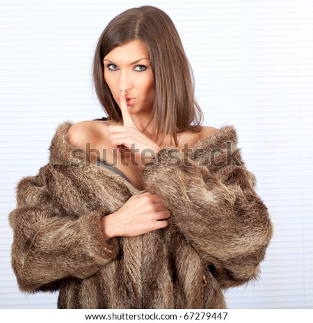 beautiful young woman in a fur coat with finger on mouths keeping silence - stock photo