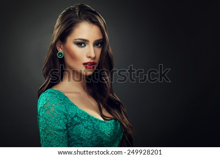 Beautiful young woman in a green dress with curly long hair - stock photo