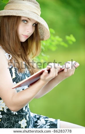 beautiful young woman  in  a hat reading a book on green background - stock photo