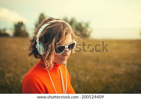 Beautiful young woman in a headphones listening music in the park. Instagram - stock photo