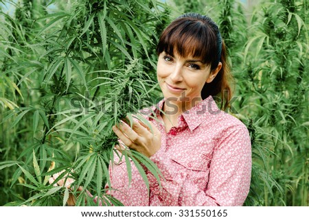 Beautiful young woman in a hemp field holding a hemp plant stem and smiling at camera - stock photo