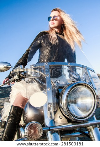 Beautiful young woman in a leather jacket riding a bike - stock photo
