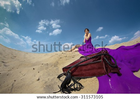 Beautiful young woman in a long purple dress on a background of blue sky, shot for the magazine, fashion, style, summer, - stock photo