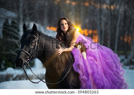 Beautiful young woman in a long purple dress with a black horse - stock photo