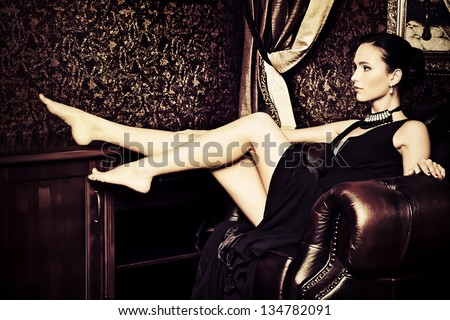 Beautiful young woman in a  luxurious classic interior. Vintage style. - stock photo