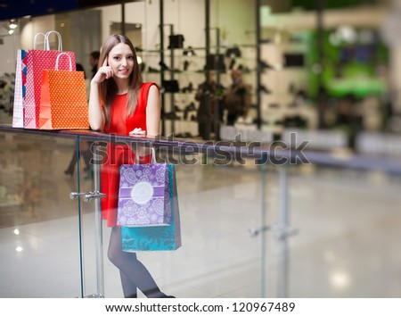 Beautiful young woman in a luxurious red dress posing with shopping bags in mall on the background of shop windows. Series. - stock photo