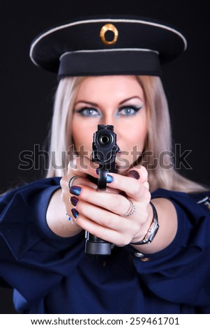 Beautiful young woman in a marine uniform with a gun over black background (focus is on the gun) - stock photo