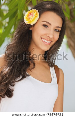 Beautiful young woman in a outdoor garden patio setting with a flower in her hair.
