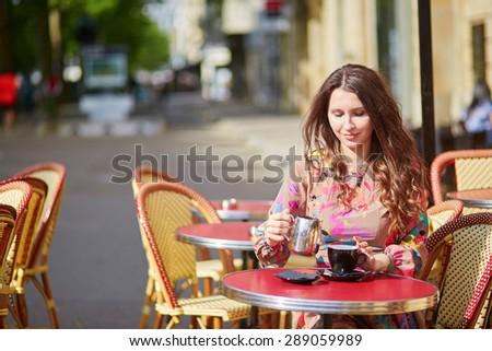 Beautiful young woman in a Parisian street cafe - stock photo