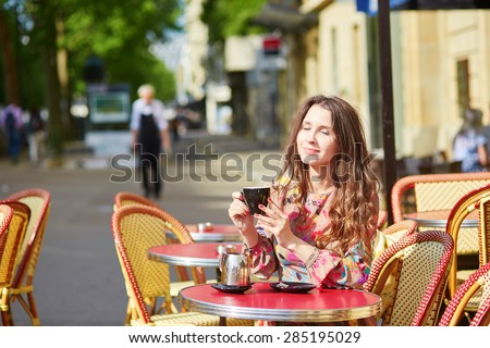 Beautiful young woman in a Parisian street cafe, enjyoing sunny week-end