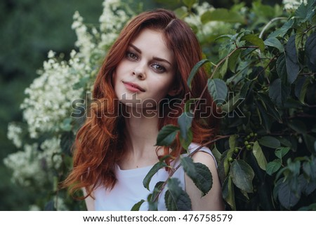 beautiful young woman in a park on a background of flowers looking into the camera