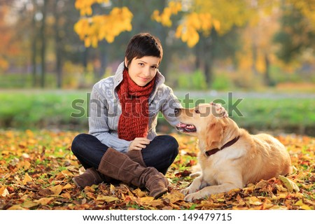 Beautiful young woman in a park with a retriever dog - stock photo